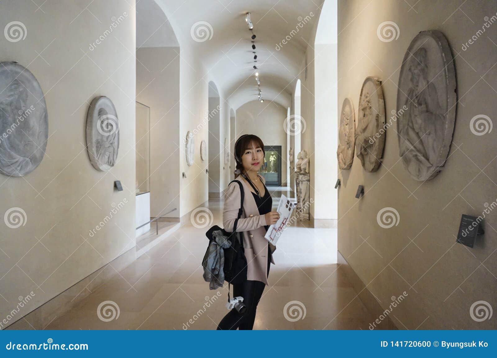 Azjatycka młoda kobieta patrzeje wokoło louvre muzeum i docenia piękno dzieło sztuki