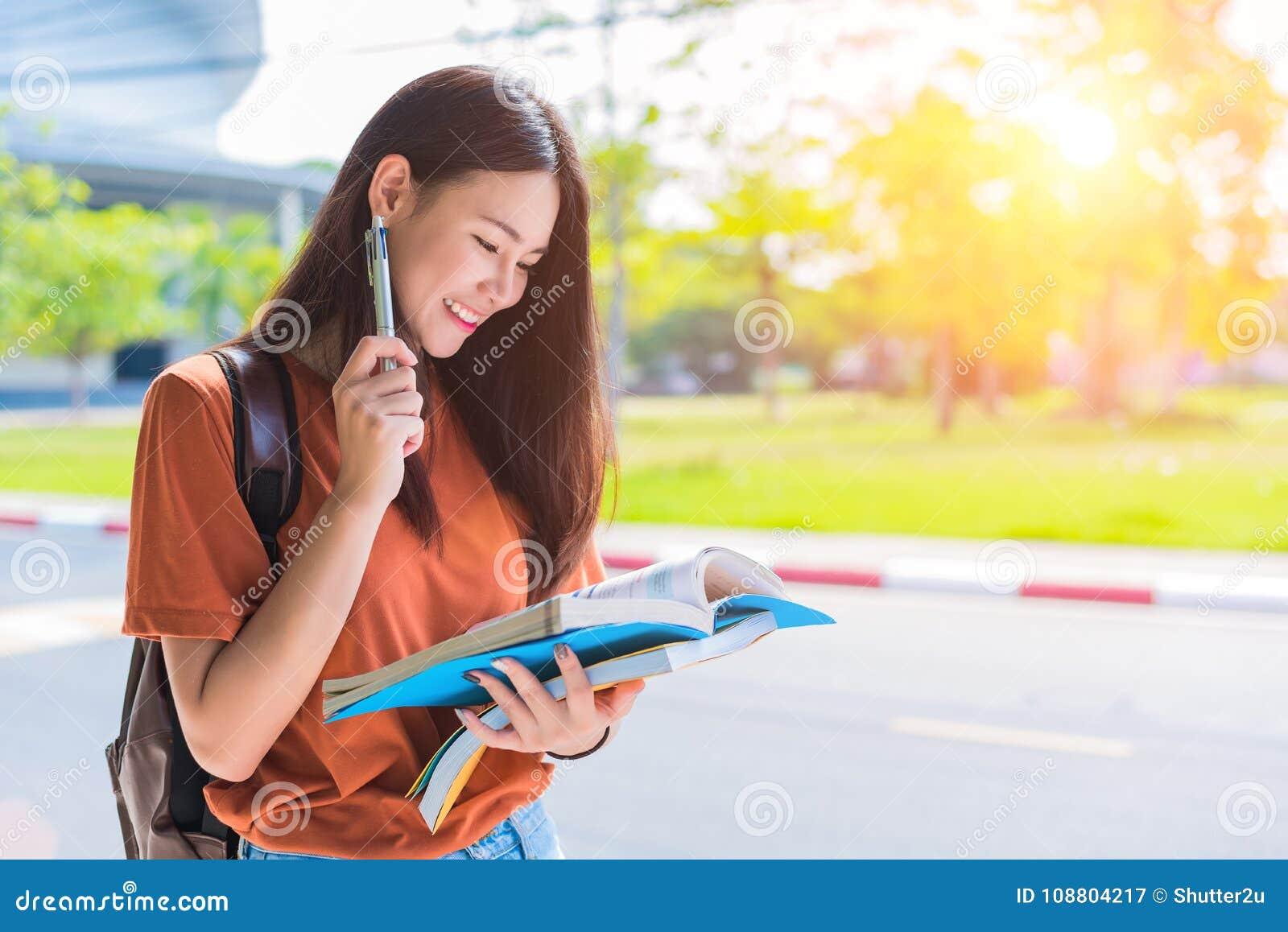 Azjatycka młoda szkoły wyższa kobieta robi pracie domowej i czytelniczym książkom dla f