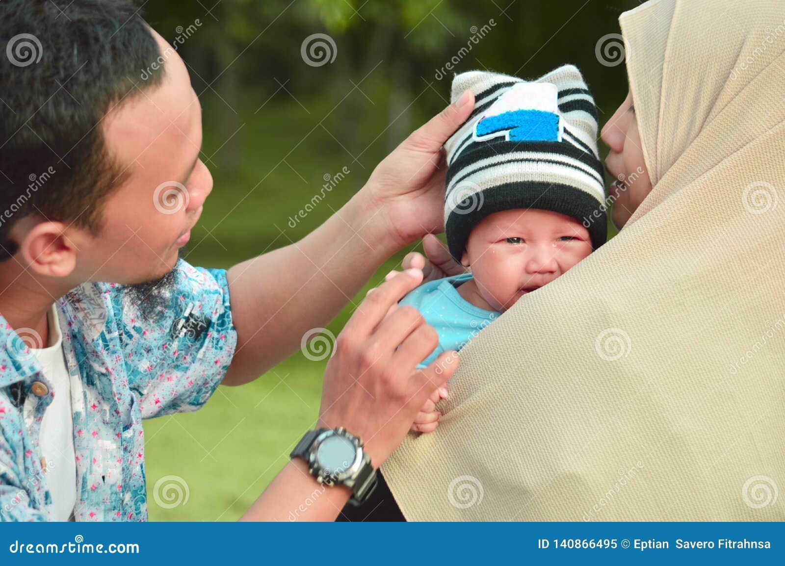 Azjatycka muzułmańska hijabi matka, ojciec i chodzimy przez parka z synem w spacerowiczu podczas gdy jego mama bierze opiekę jej