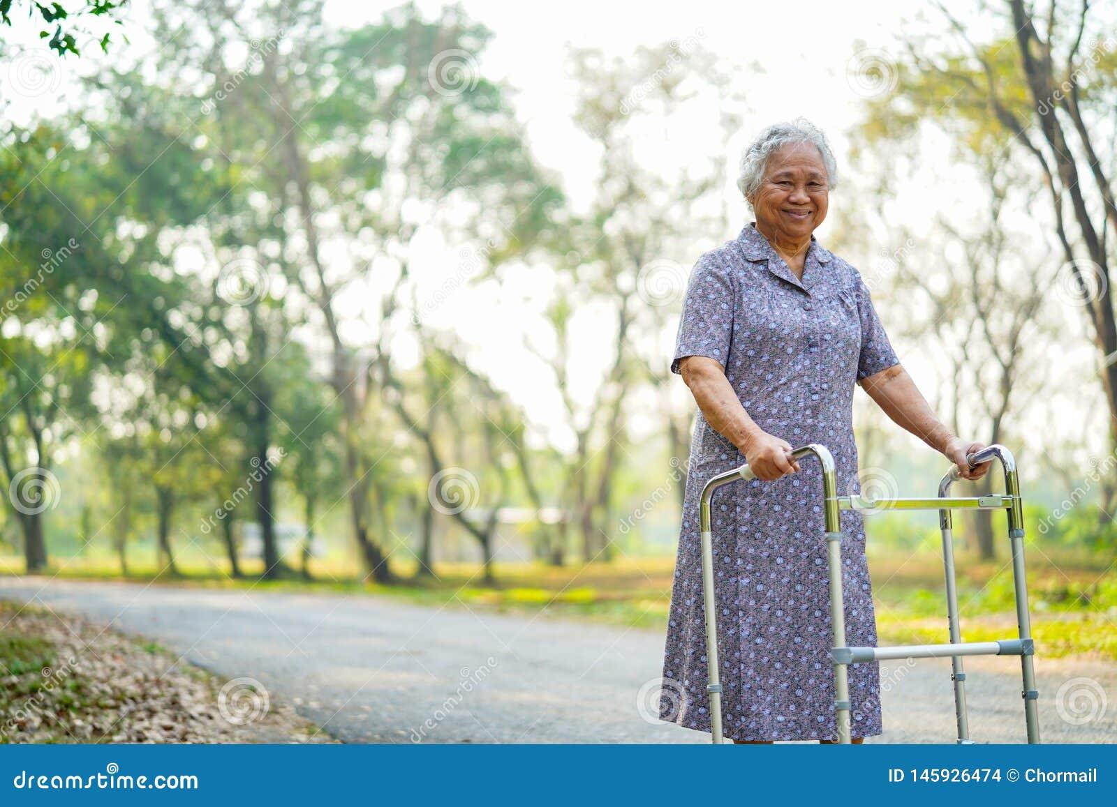 Azjatycka pielęgniarki physiotherapist lekarki opieka, senior lub starszej starej damy kobiety cierpliwy spacer z piechurem przy