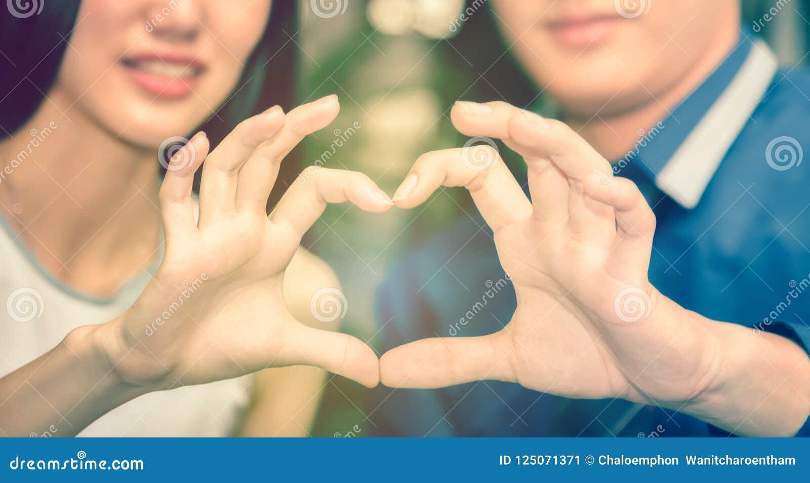 Azjatycka samiec i żeńskie pary symbolizujemy rękę z sh
