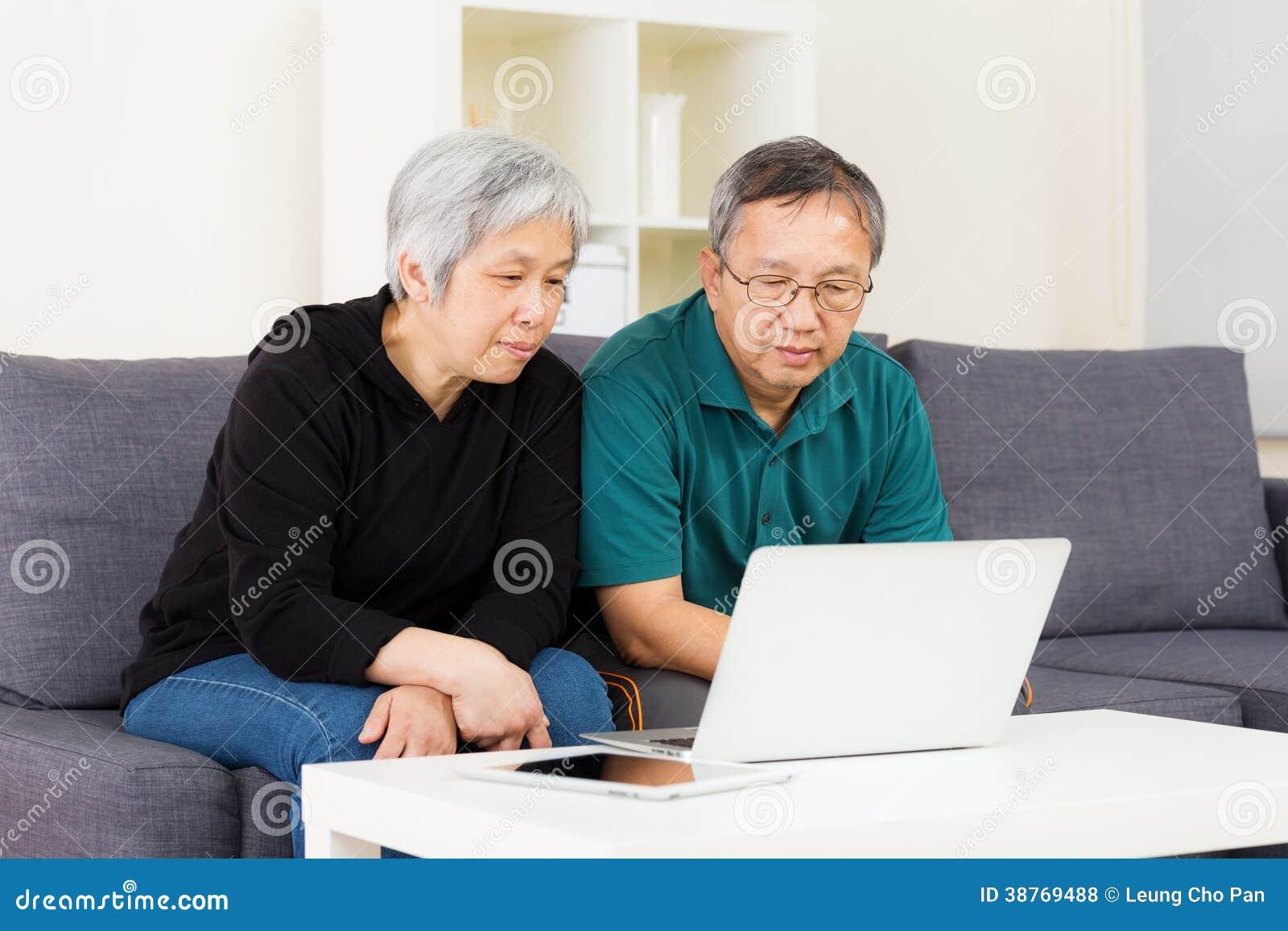 Azjatycka stara para używa laptop