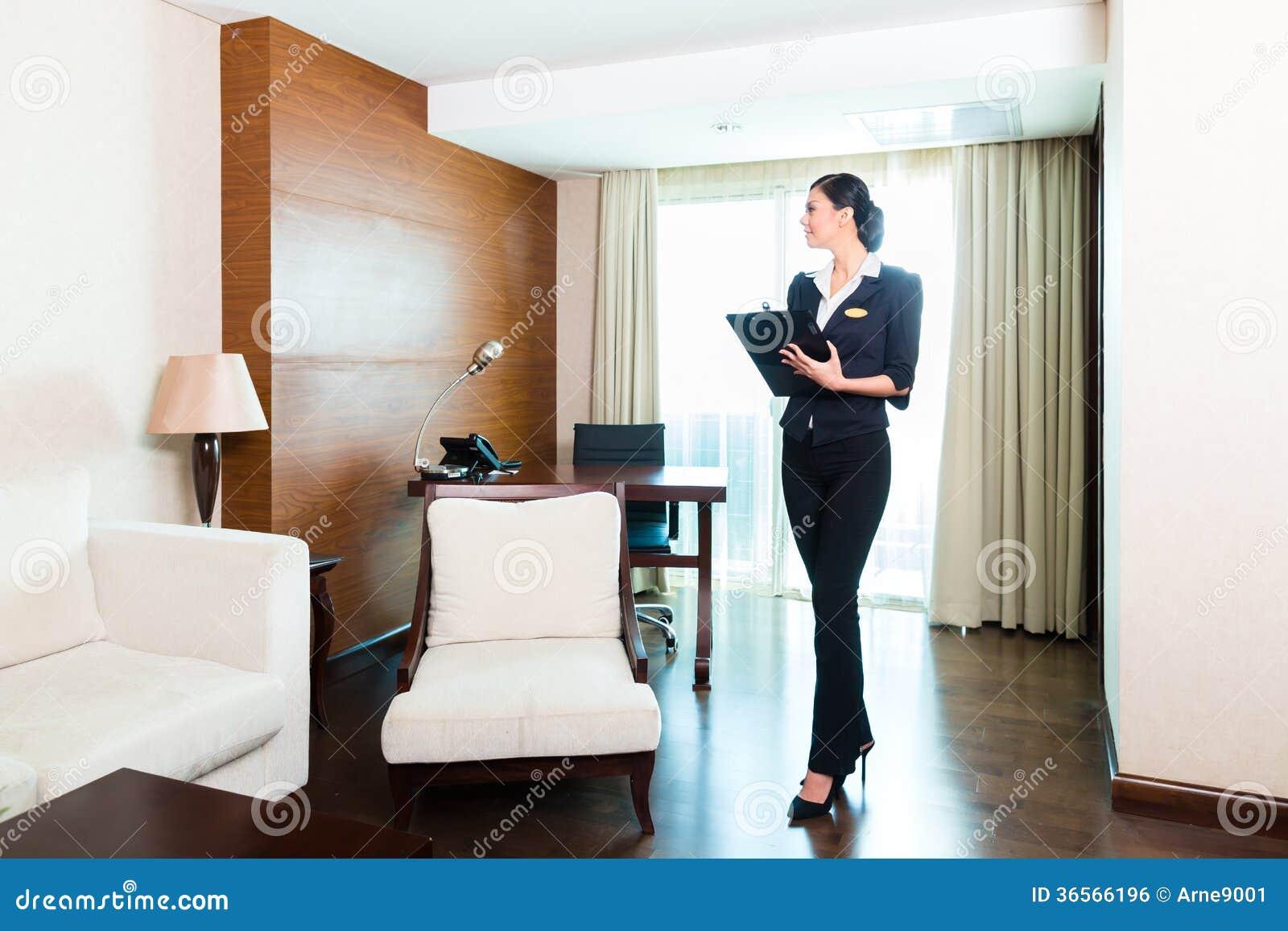 Azjatycka wykonawcza gospodyni kontroluje pokój hotelowego
