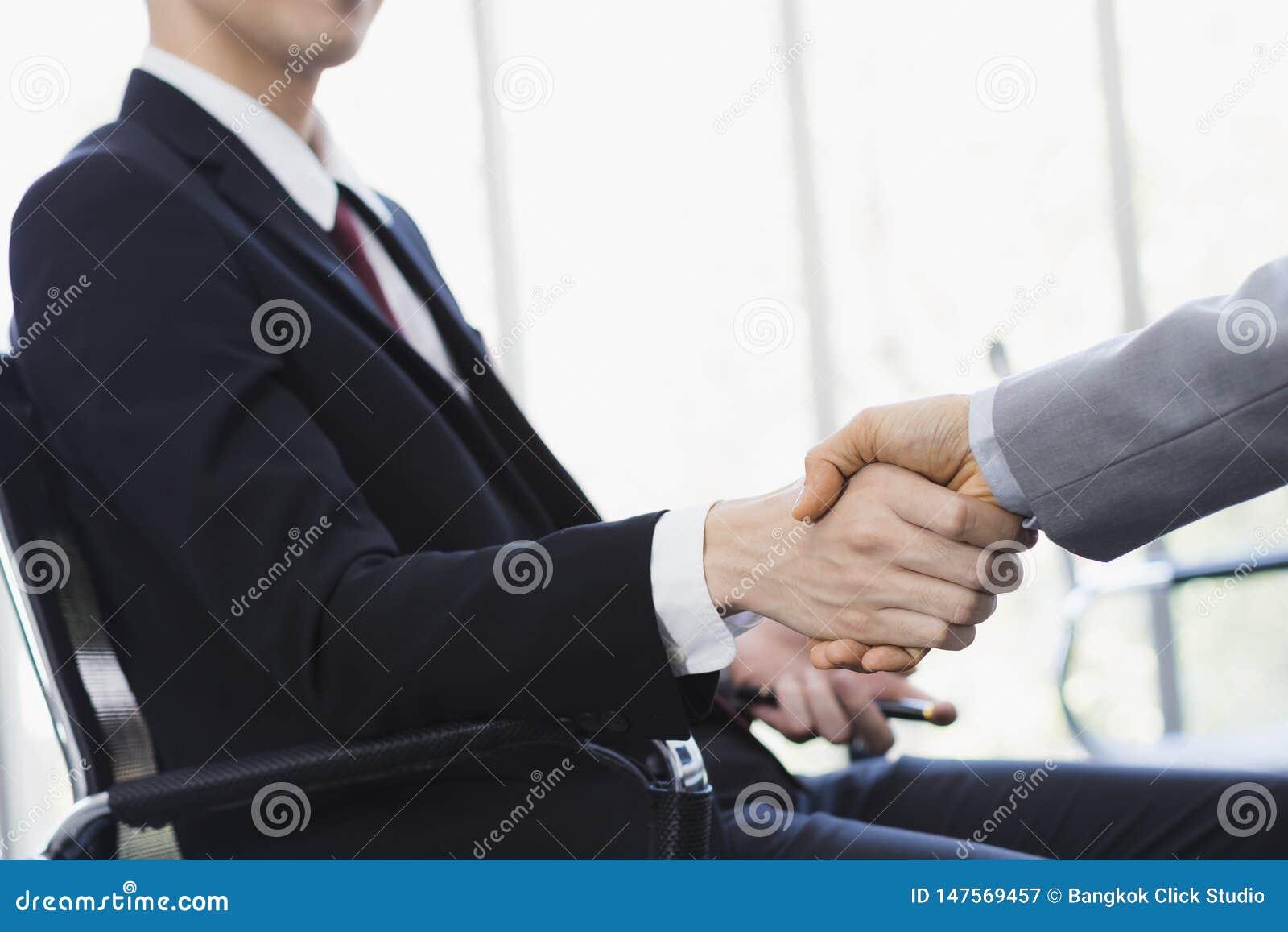Azjatycki biznesmena u?cisk d?oni wp?lnie w biurze