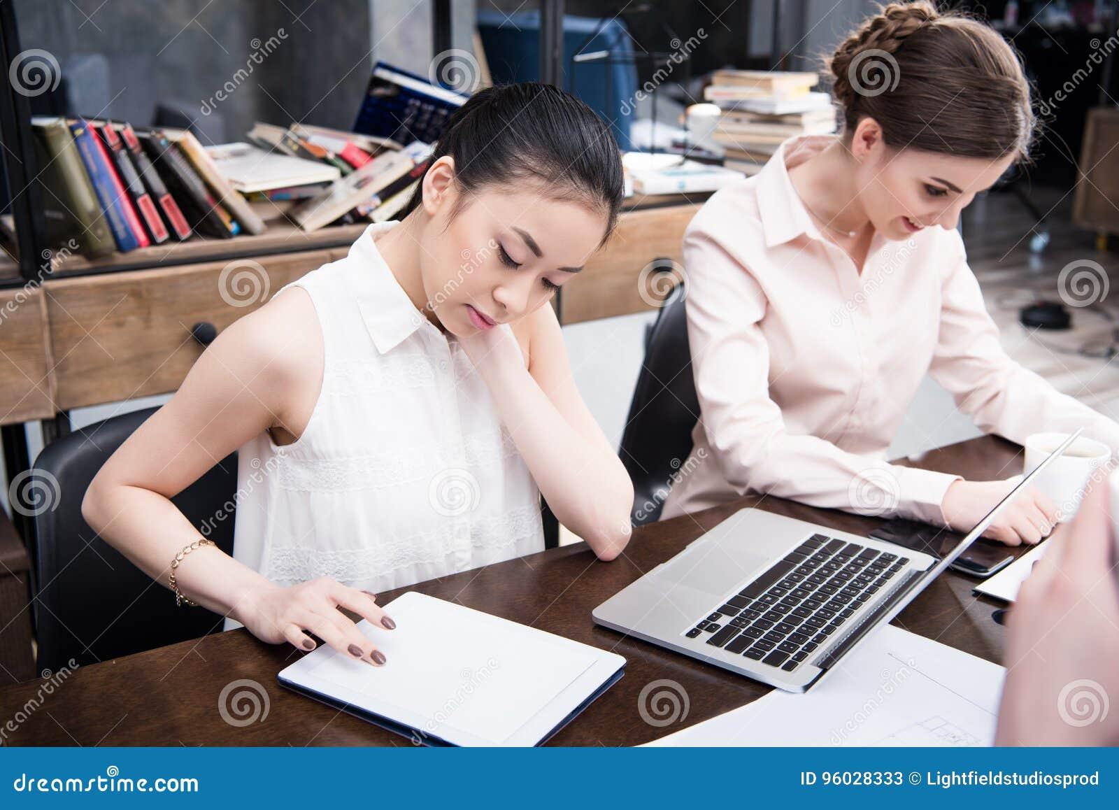 Azjatycki bizneswoman pracuje z cyfrową pastylką podczas gdy jej koledzy pracuje blisko w nowożytnym biurze