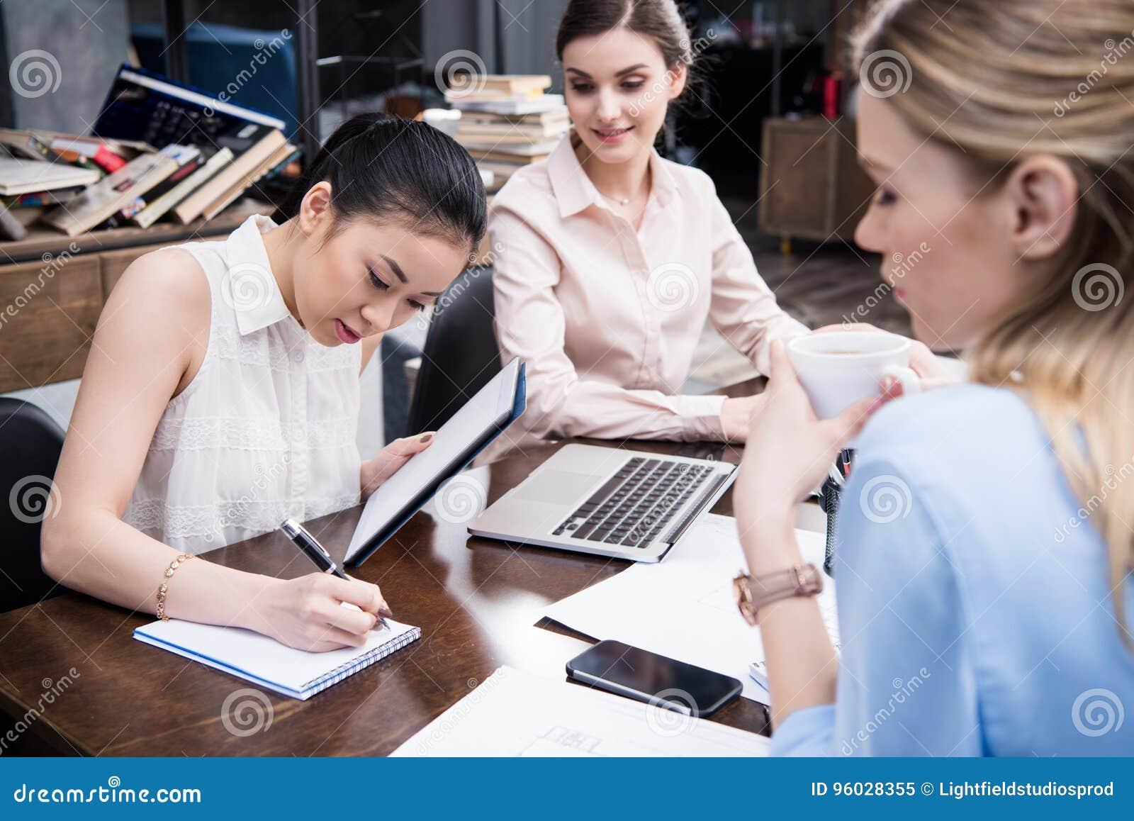 Azjatycki bizneswomanu writing coś w notepad podczas gdy jej koledzy pracuje blisko w nowożytnym biurze