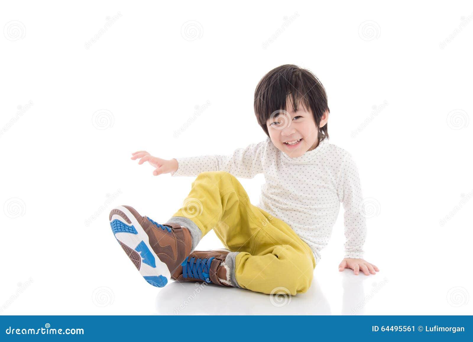Azjatycki chłopiec obsiadanie na białym tle odizolowywającym