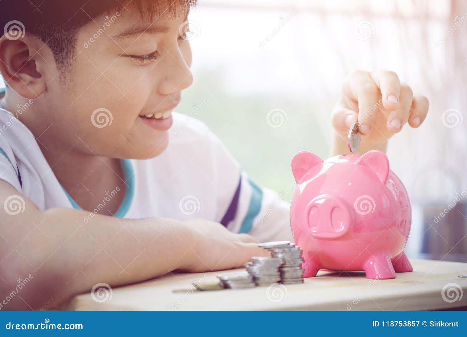 Azjatycki chłopiec oszczędzania pieniądze w różowym prosiątko banku