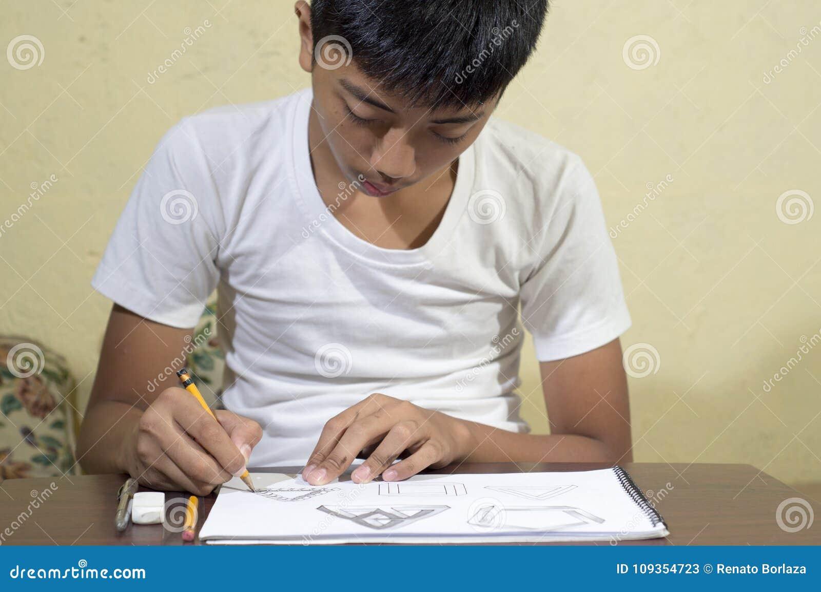 Azjatycki chłopiec uczenie i ćwiczyć rysować 3D kształty na rysunkowym notatniku