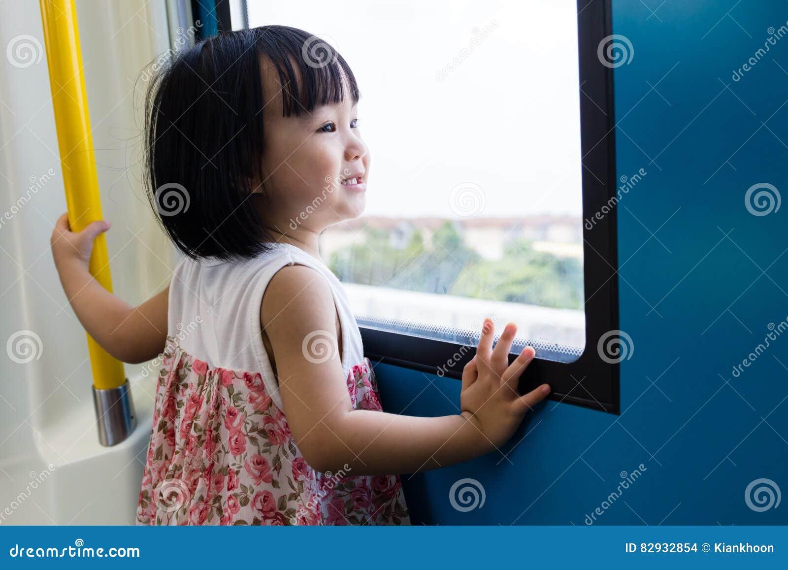 Azjatycki Chiński małej dziewczynki inside pociąg patrzeje obok okno