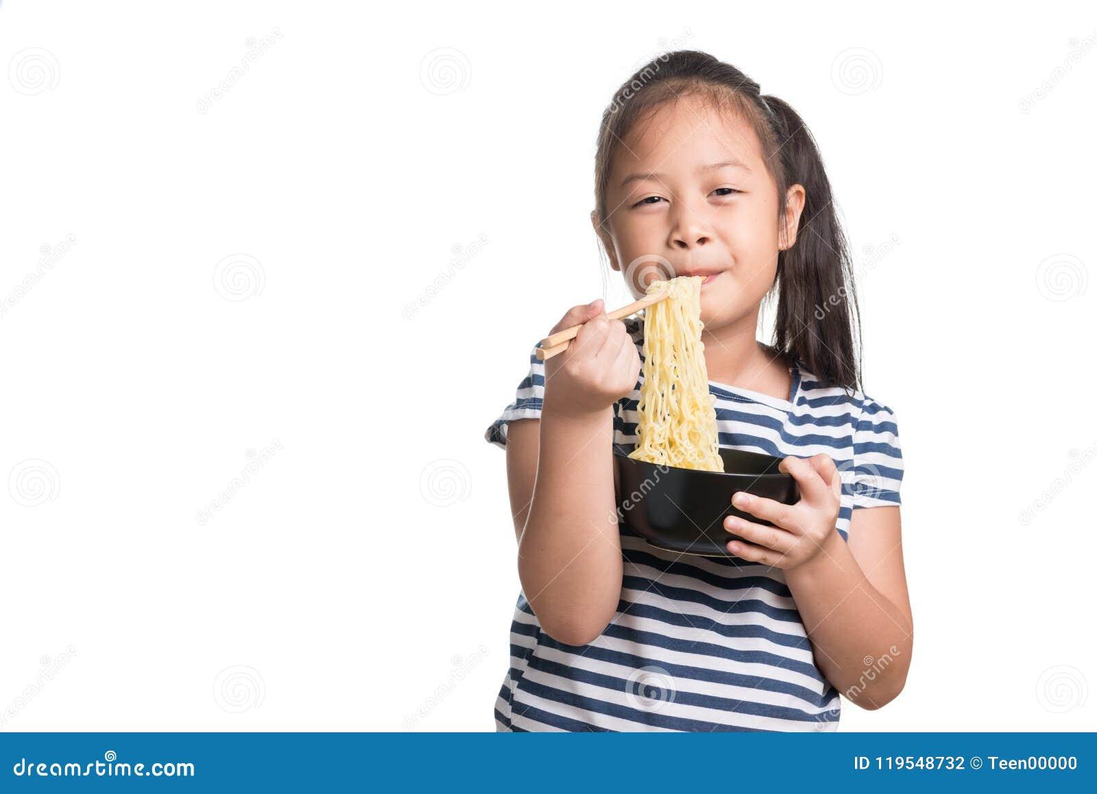 Azjatycki dziecko dziewczyny wiek 7 rok, je Natychmiastowych kluski na białym b