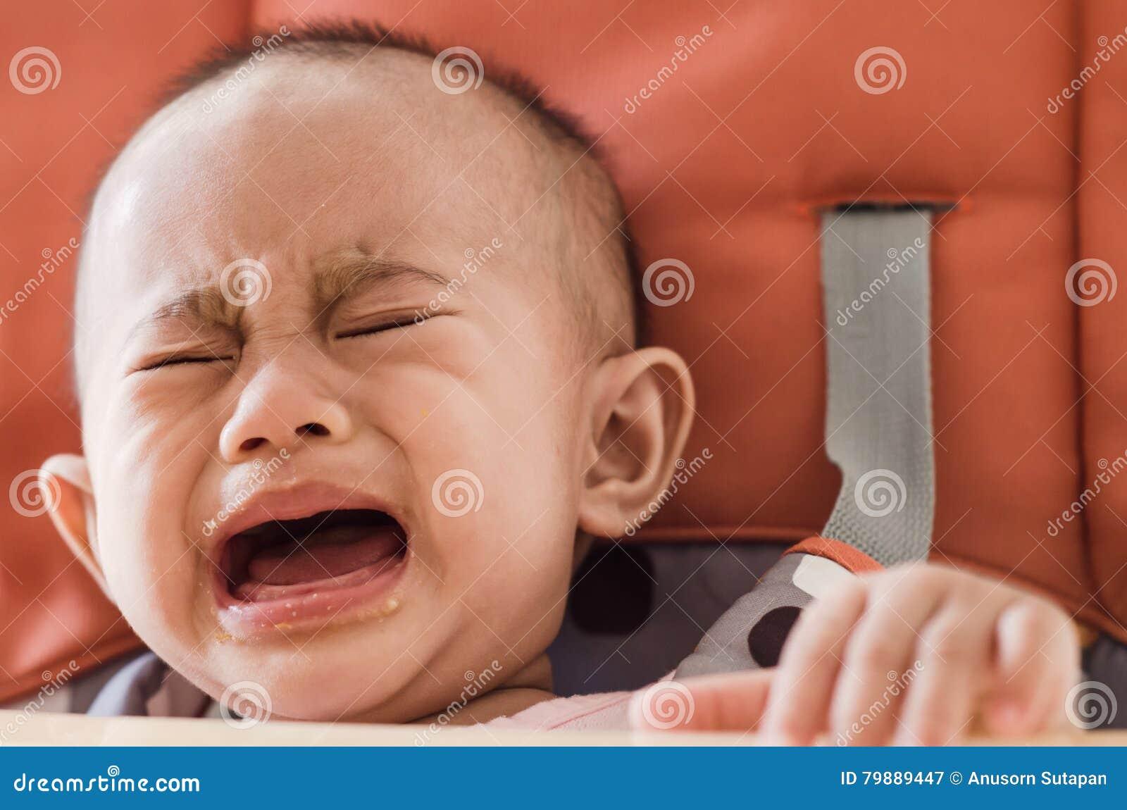 Azjatycki dziewczynki obsiadanie w highchair i płaczu odmawia jeść f
