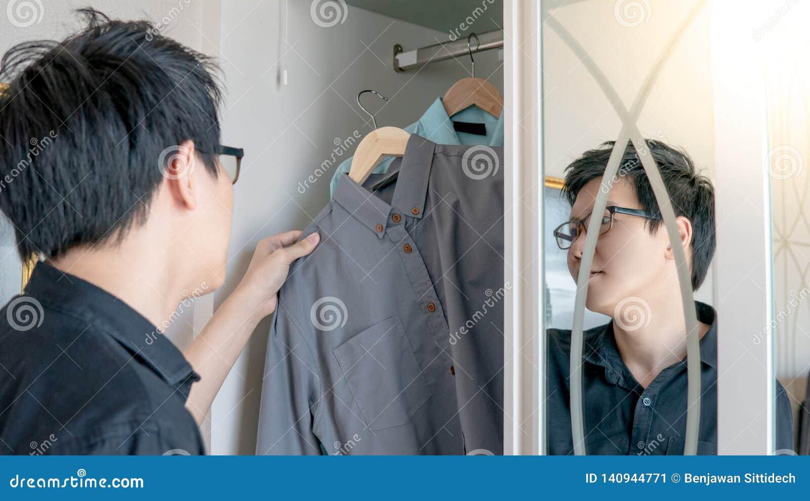Azjatycki mężczyzna wybiera koszula w szafie