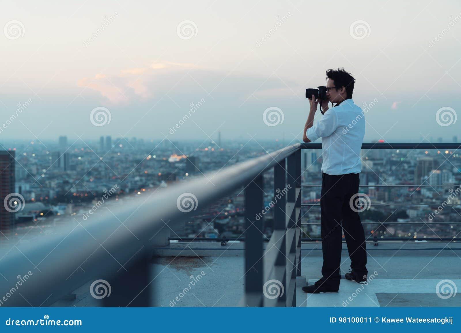 Azjatycki mężczyzna bierze pejzaż miejski fotografię na budynku dachu w niskiego światła sytuaci Fotografia, biurowi ludzie lub h