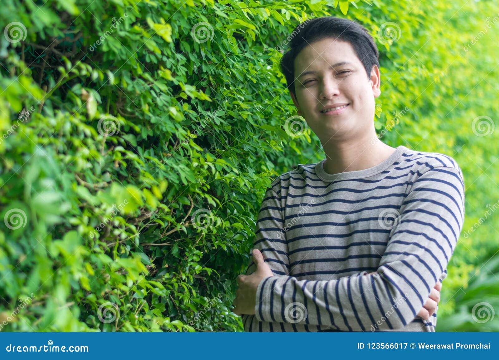 Azjatycki mężczyzna stoi jego szczęśliwy ono uśmiecha się i pokazuje