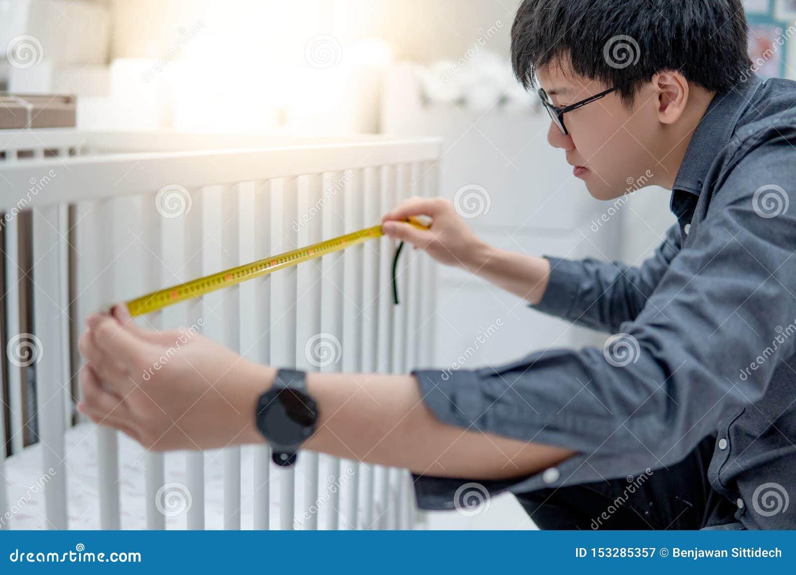 Azjatycki mężczyzna używa taśmy miarę na berbeci łóżkowych poręczach
