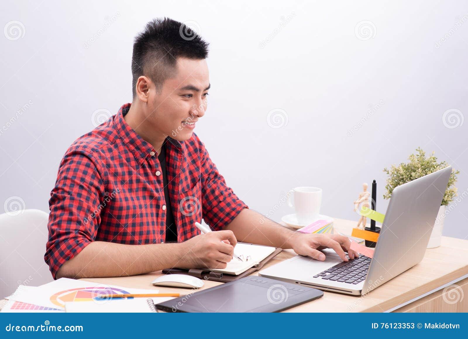 Azjatycki mężczyzna Writing Przy biurkiem W Ruchliwie Kreatywnie biurze