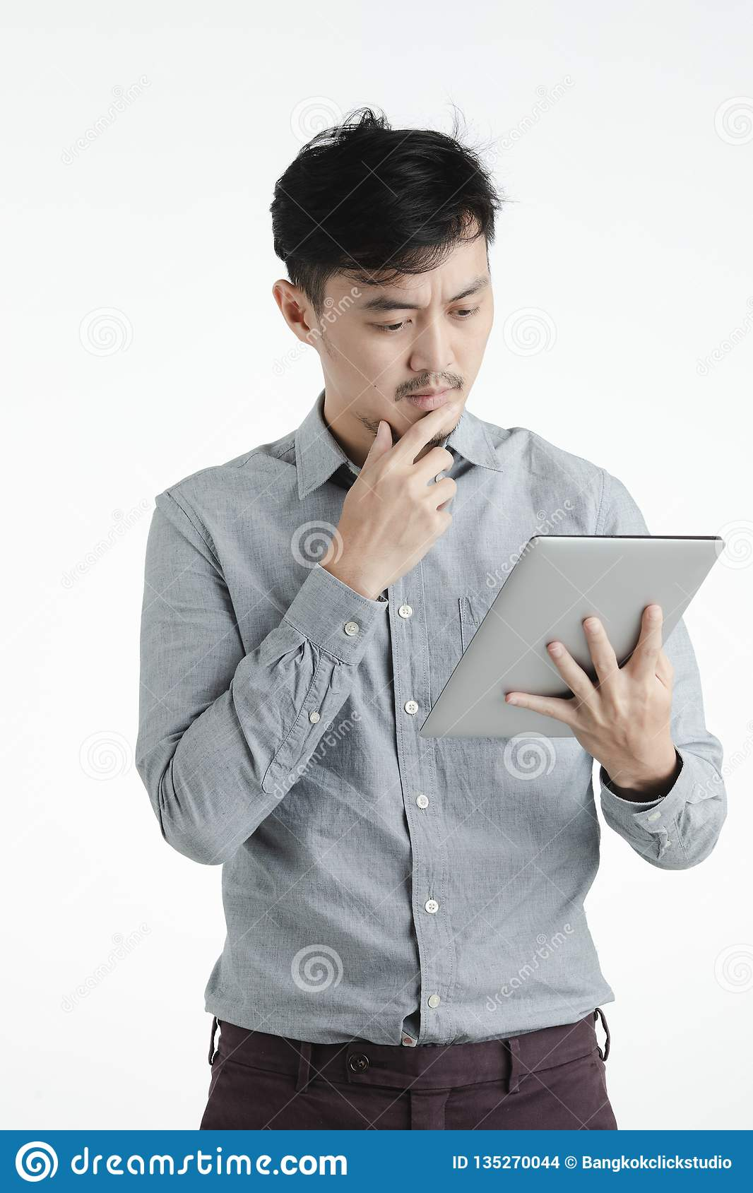 Azjatycki młody człowiek używa pastylkę