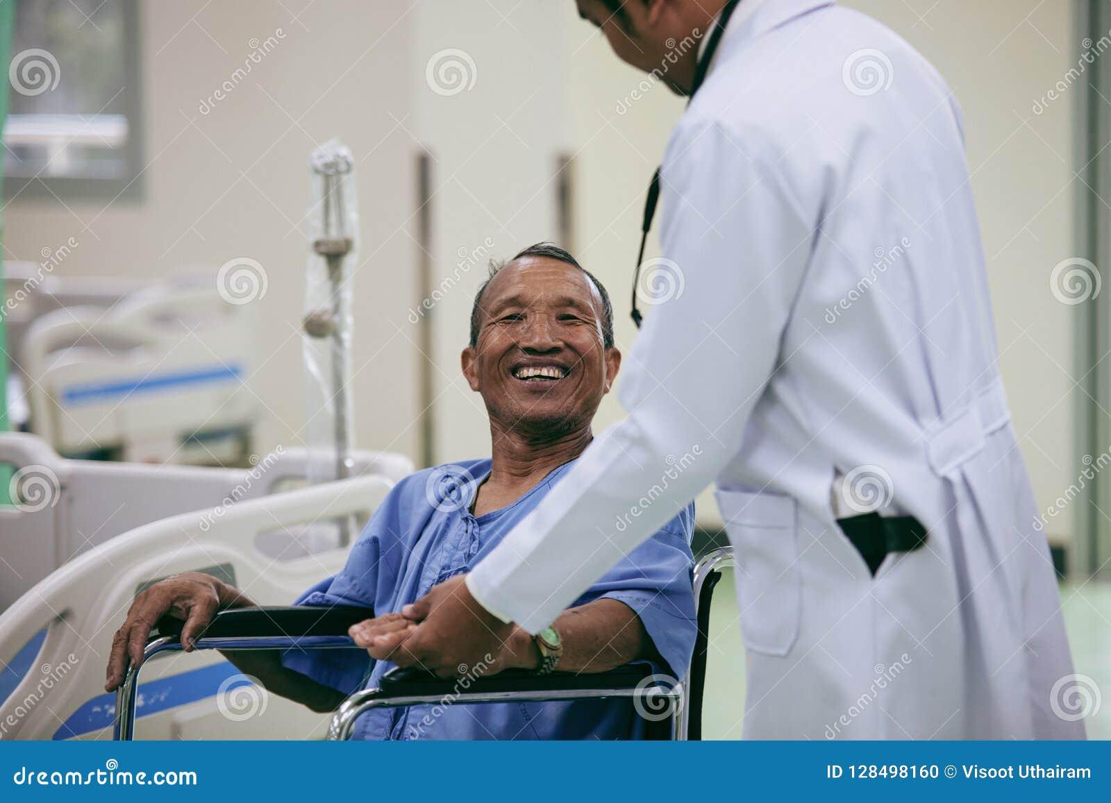 Azjatycki pacjent w wózka inwalidzkiego obsiadaniu w szpitalu z Azjatyckim docto