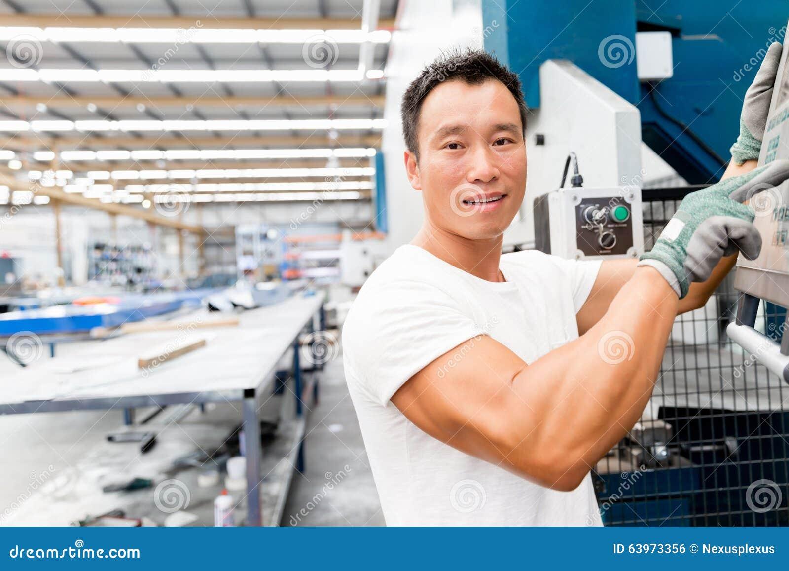 Azjatycki pracownik w produkci roślinie na fabryce