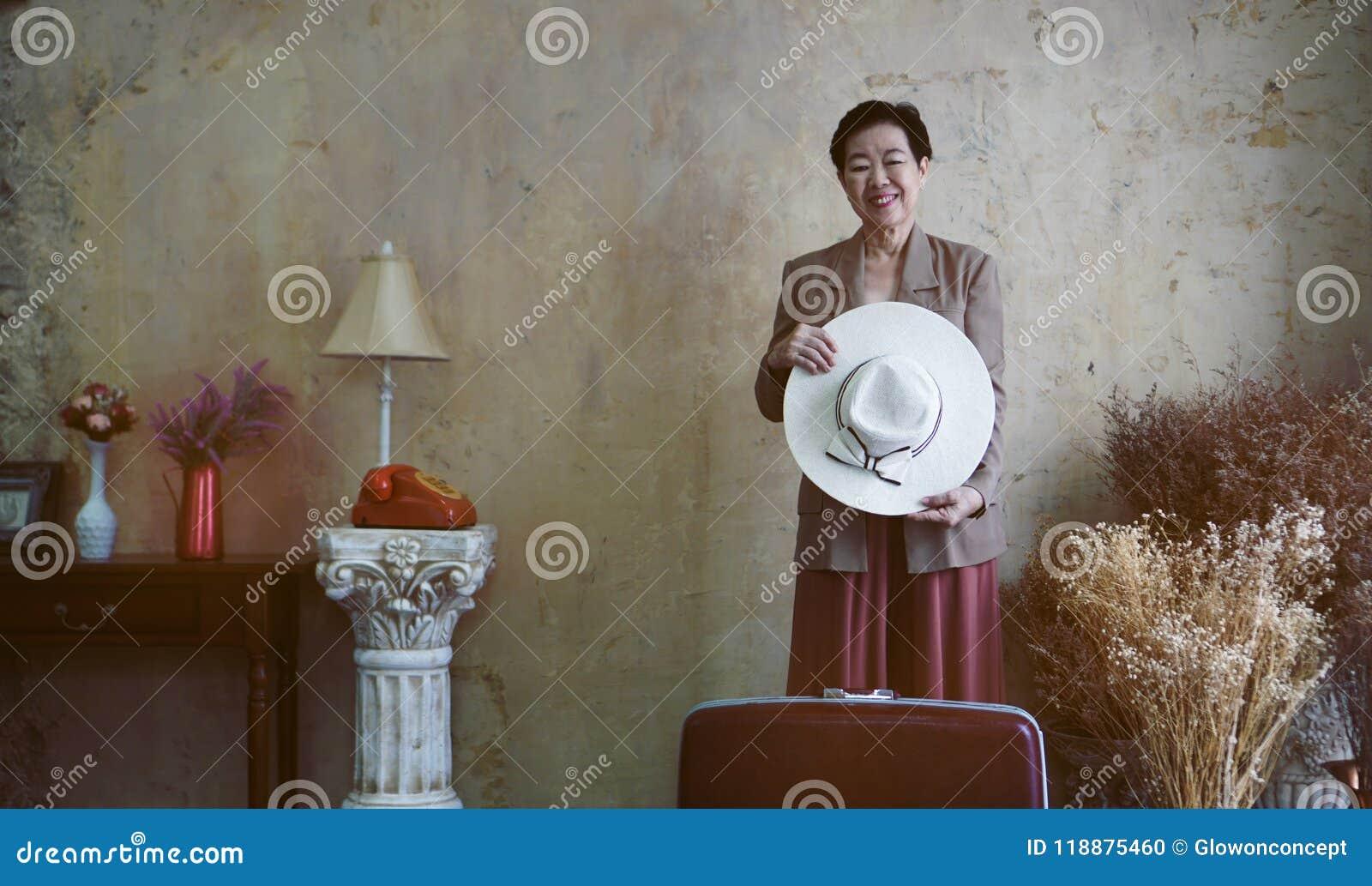 Azjatycki starszy kobieta rocznika kapelusz, retro moda z podróży luggag