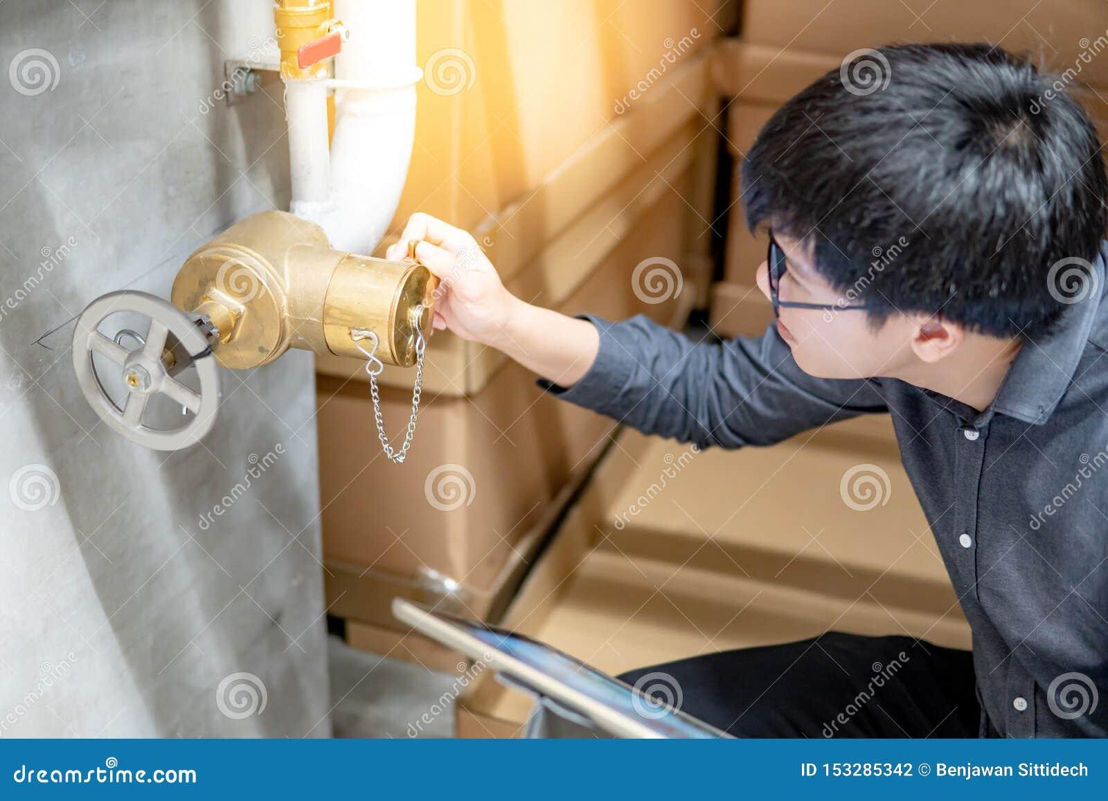 Azjatycki technik sprawdza wodnej bramy klapę
