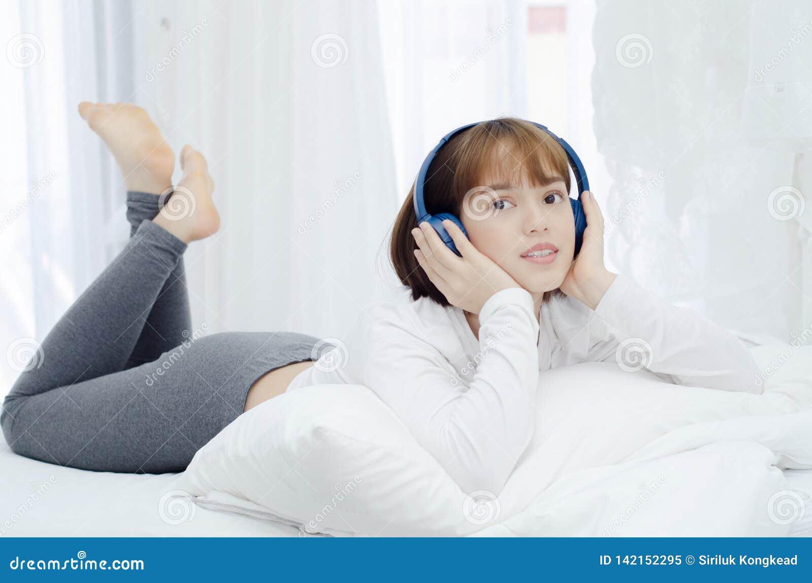 Azjatyckie kobiety odpoczywać w pokoju Był uśmiechnięta i słuchanie muzyka