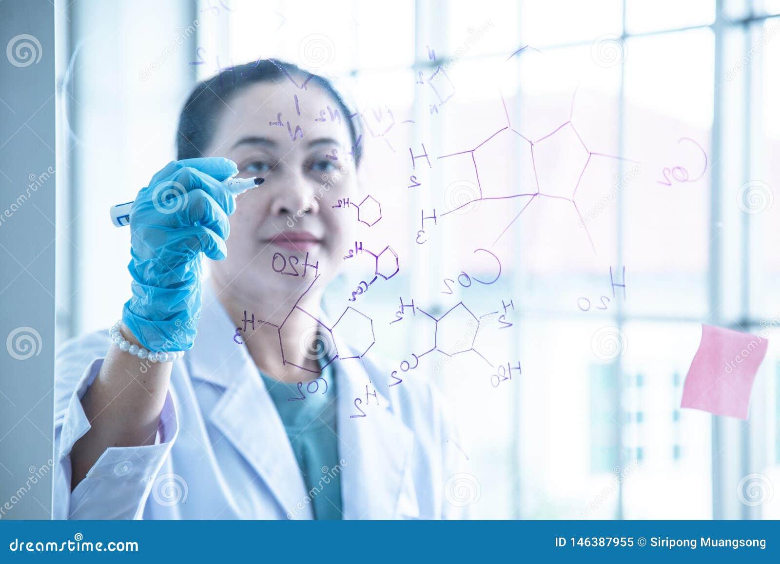 Azjatyckiej kobiety chemiczny naukowiec pisze formular na szkło desce