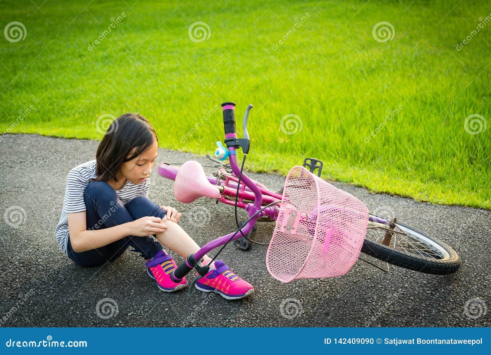 Azjatyckiej małej dziewczynki siedzący puszek na drodze z noga bólu opłatą rowerowy wypadek roweru spadek blisko dziecka, dziewcz