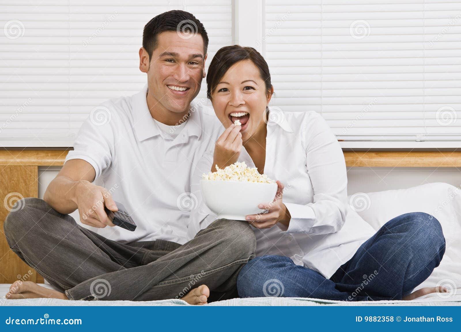 Azjatykci atrakcyjny łóżkowy pary łasowania popkorn
