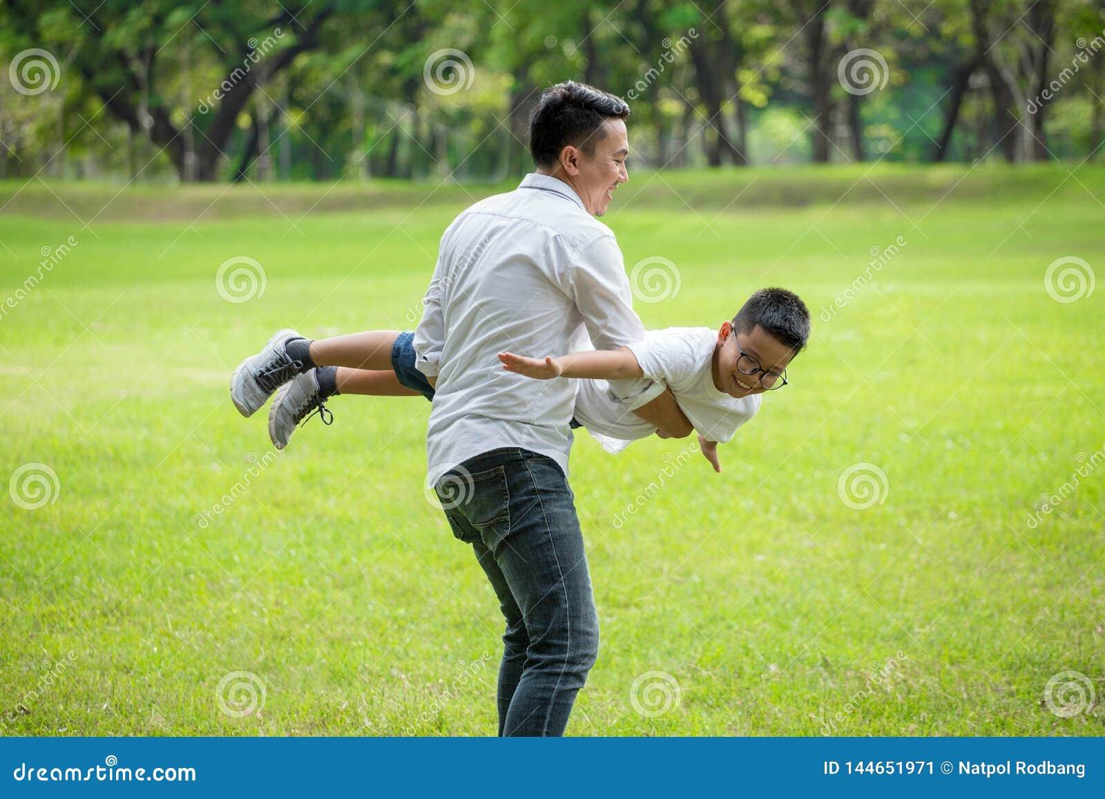 Azjatykci szcz??liwa rodzina Ojciec i syn ma zabawę w parku bawić się i rozciąga za rękach udaje latać wpólnie tata