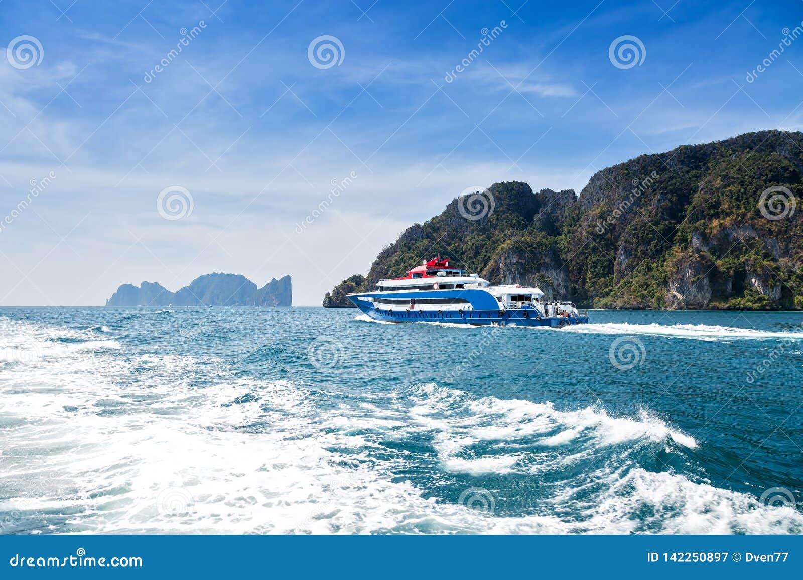 Azul com o barco branco e vermelho da velocidade do prazer dos acentos Navigação no mar contra uma ilha tropical Vista traseira T