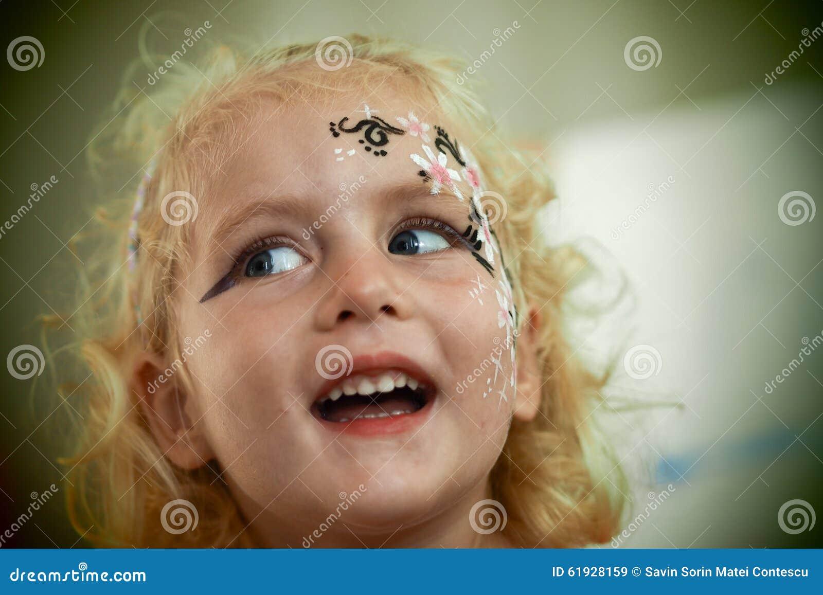 Azul louro pequeno a pintura eyed da cara da menina está sorrindo