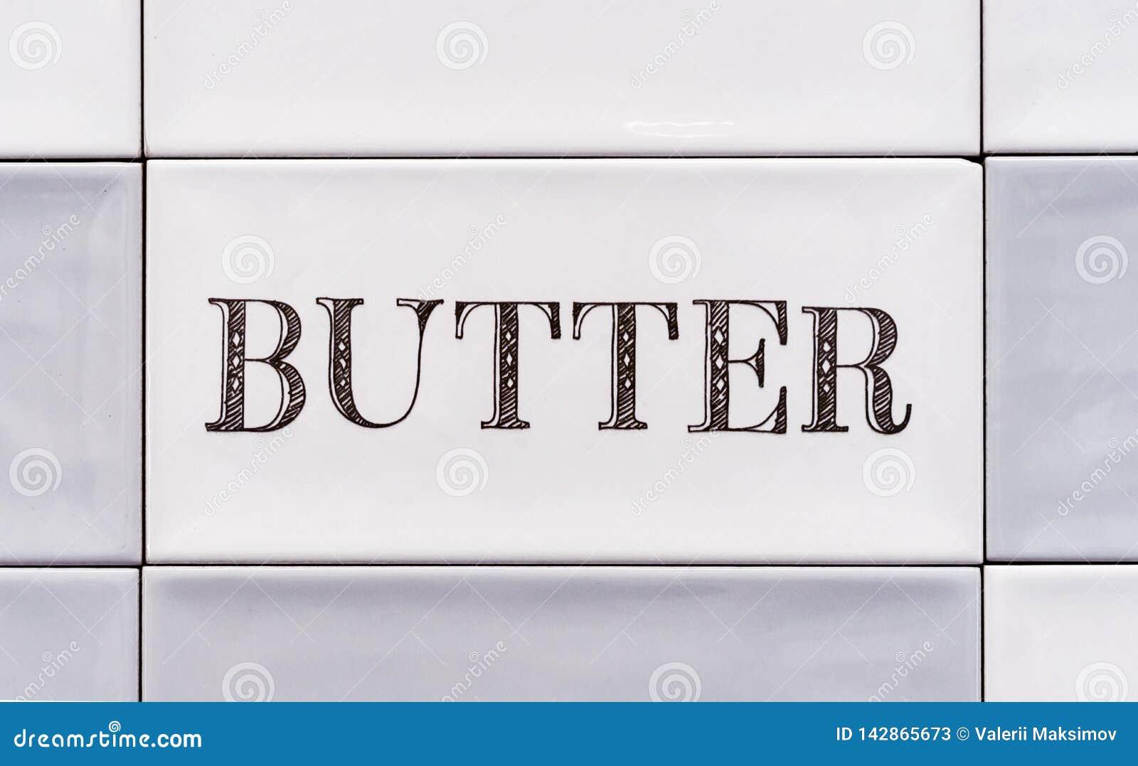 Azulejo com a manteiga da inscrição Fundo e textura dos azulejos
