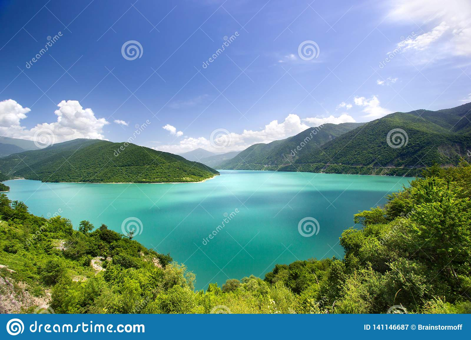 Azure water in a blue lagoon among green mountains blue sky white clouds background