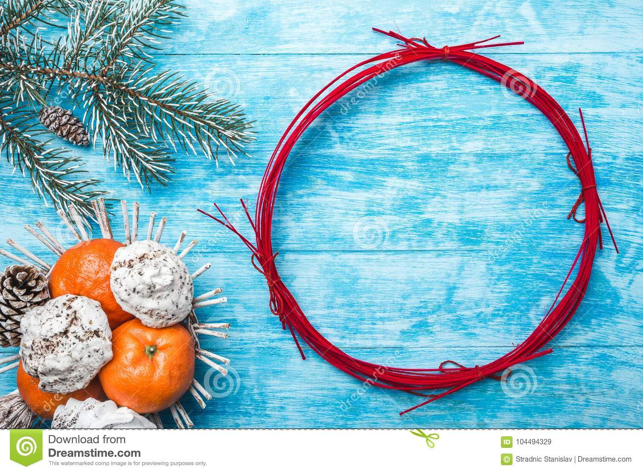 Azure wood background. Green fir tree. Fruit with mandarin and sweets. Circle for Christmas or New Year.