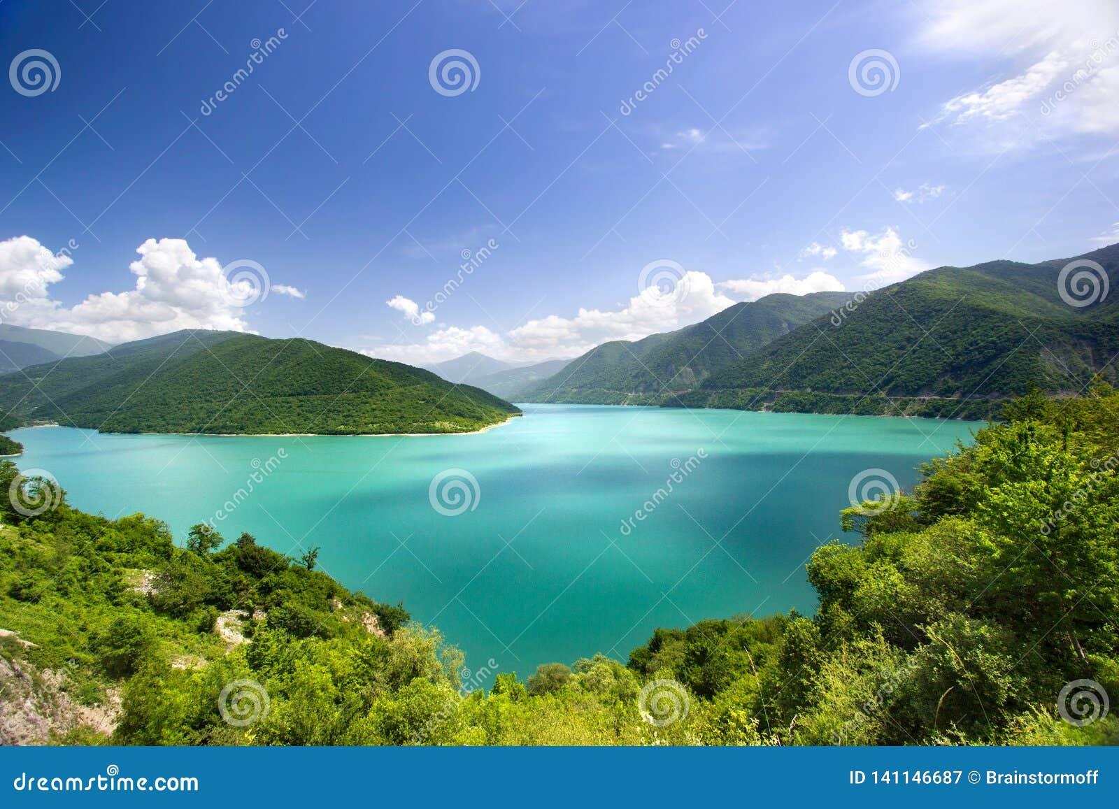 Azurt vatten i en blå lagun bland grön bakgrund för moln för blå himmel för berg vit