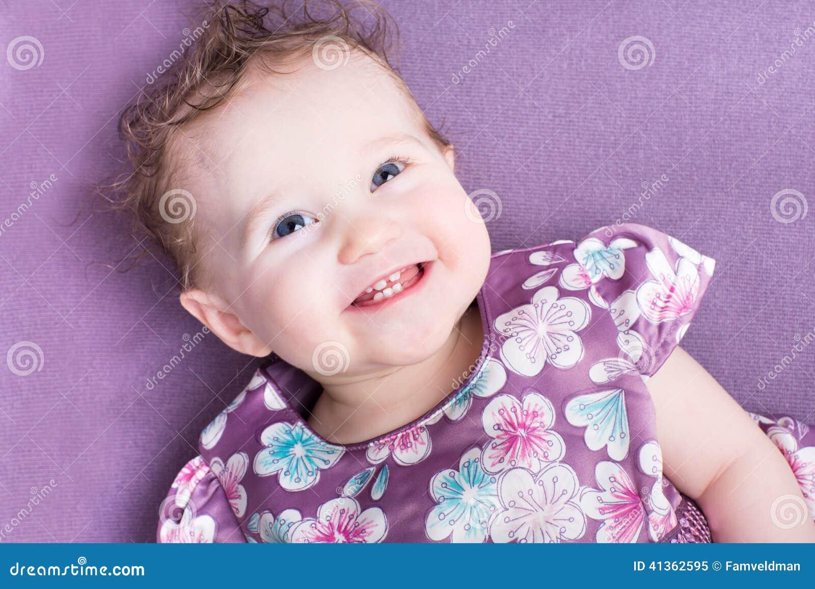 Célèbre Bébé Avec Les Cheveux Bouclés Portant Une Robe Pourpre Photo stock  BR61