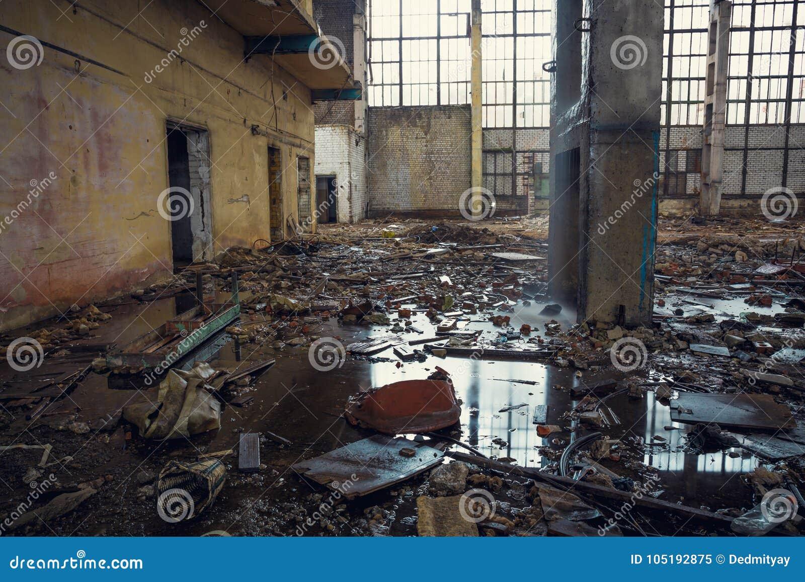 Bâtiment industriel ruiné avec des magmas au sol, entrepôt abandonné rampant