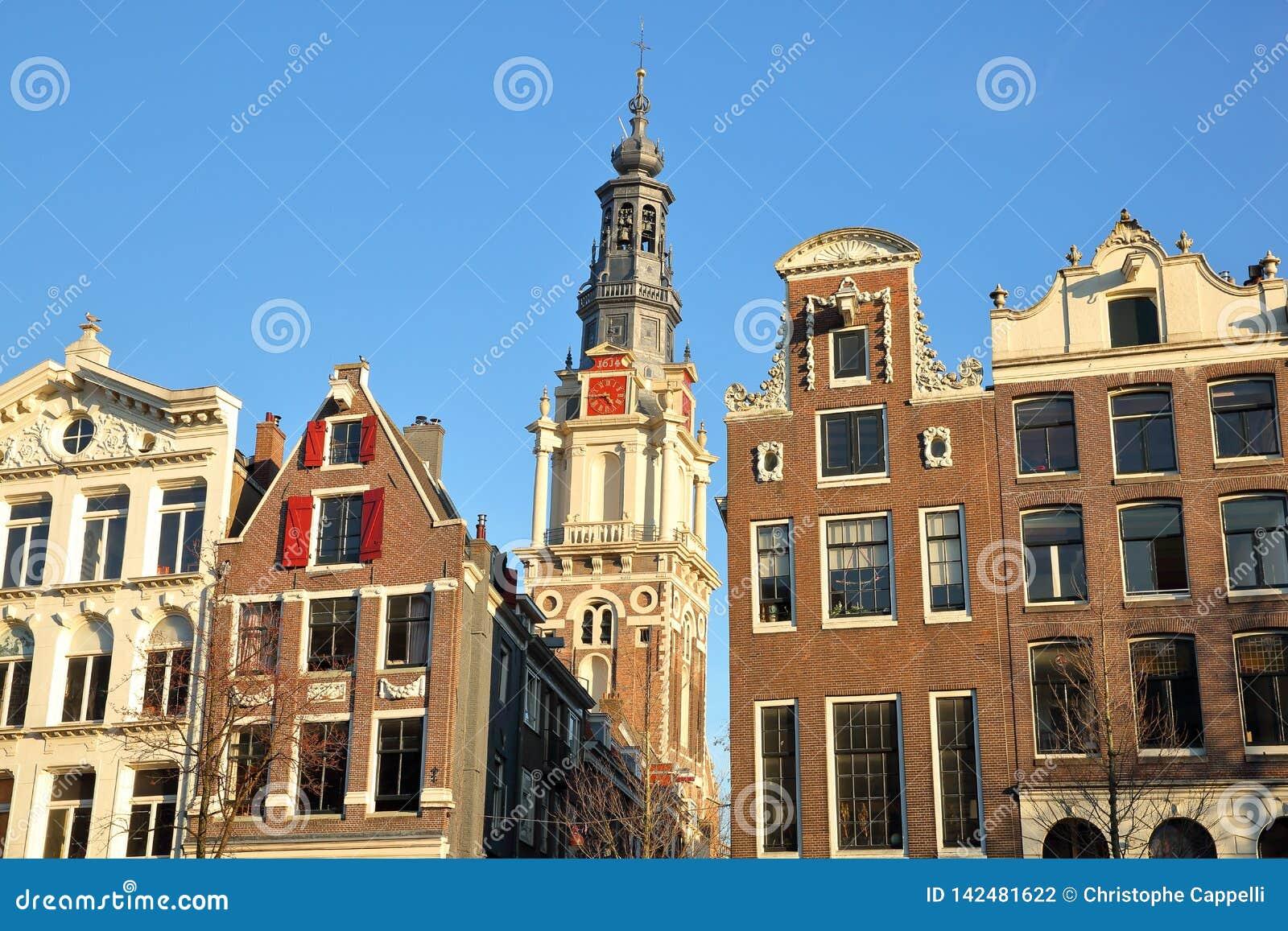 Bâtiments tordus et colorés d héritage, situés le long du canal de Kloveniersburgwal, avec le clocktower d église de Zuiderkerk d