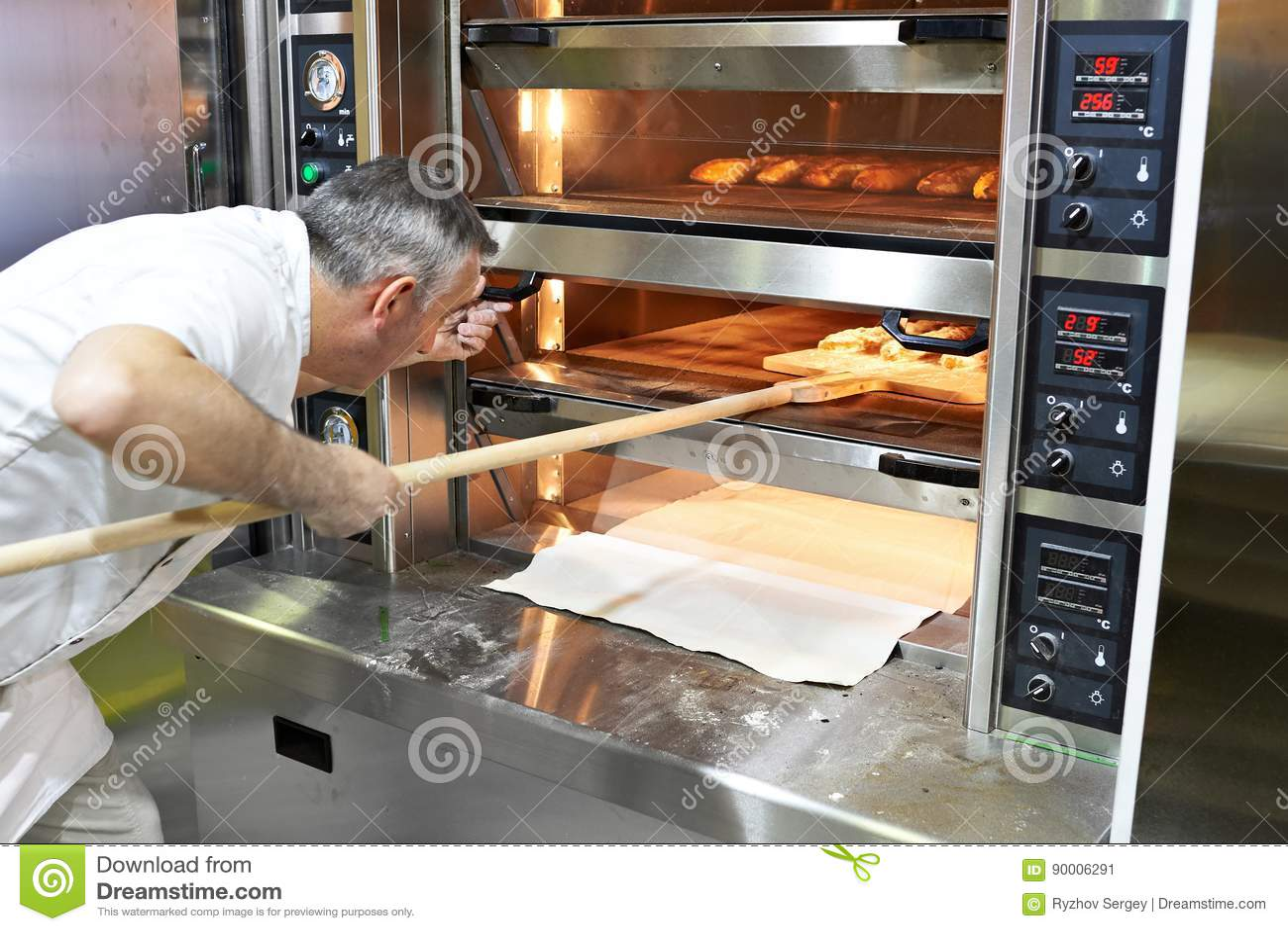 Bäcker backt Brot im Ofen