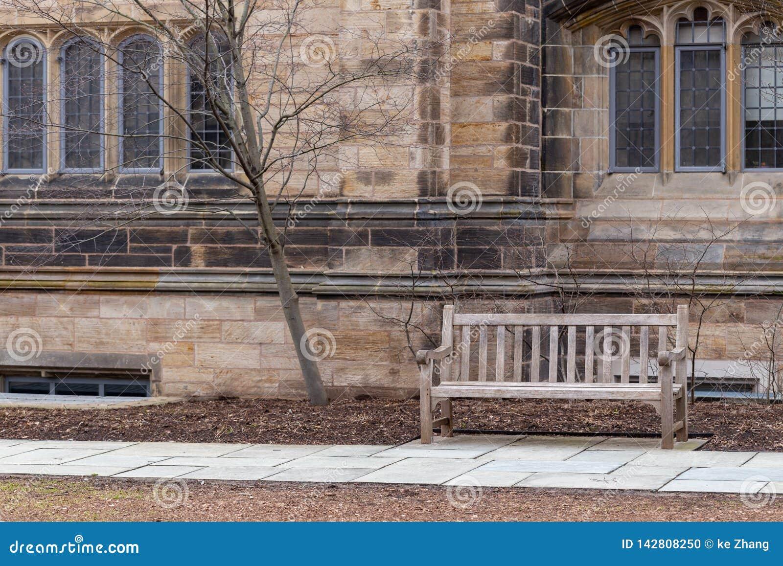 Bänk på stengångbanan mot gammal dekorativ byggnad