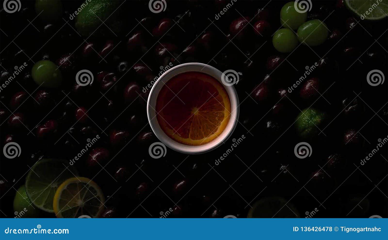 Bär i vattendroppar med körsbär, gröna druvor, orange skiva, limefrukt, citronskivor