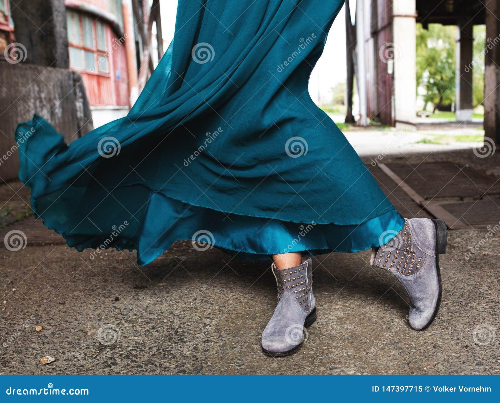 Bära en turkos, i vinden som fladdrar klänningen, gråa ankelkängor som fotograferas till midjan