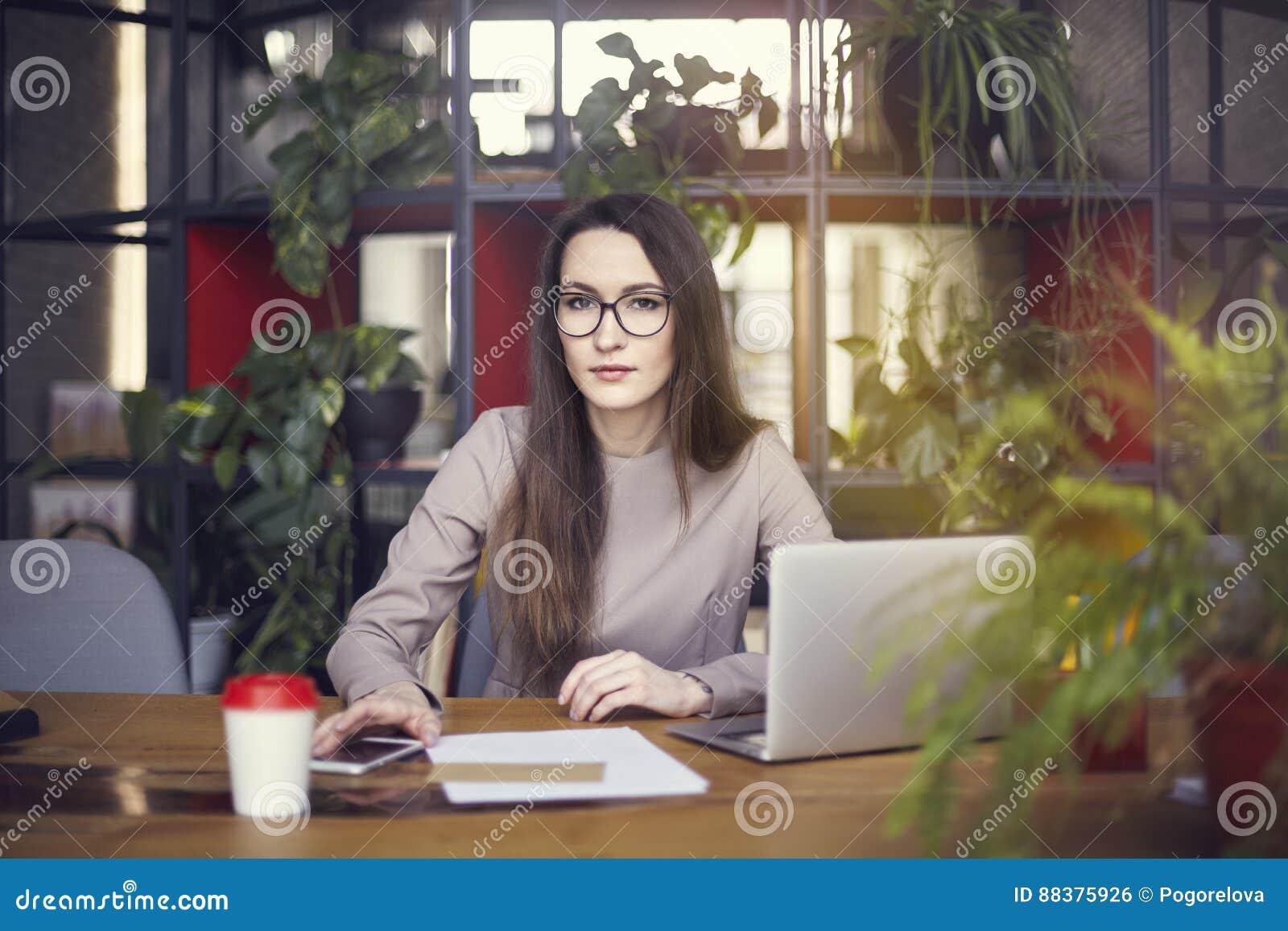 Bärande ögonexponeringsglas för härlig flicka i coworking studio Använda bärbara datorn och smartphonen på trätabellen Begrepp av
