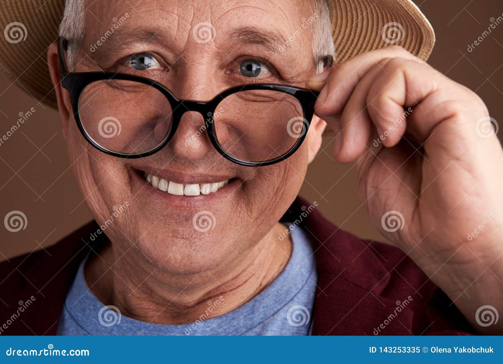Bärande exponeringsglas för positiv man och le, medan trycka på dem