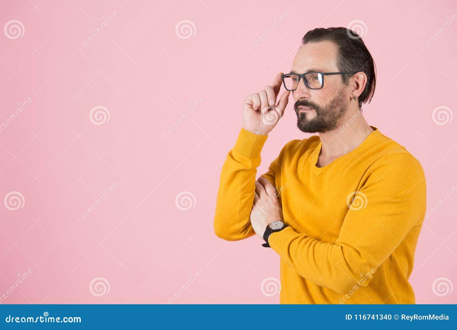 Bärande exponeringsglas för stilig freelancer som ser av till rätten av ramen Man med exponeringsglas som söker analytiskt uttryc