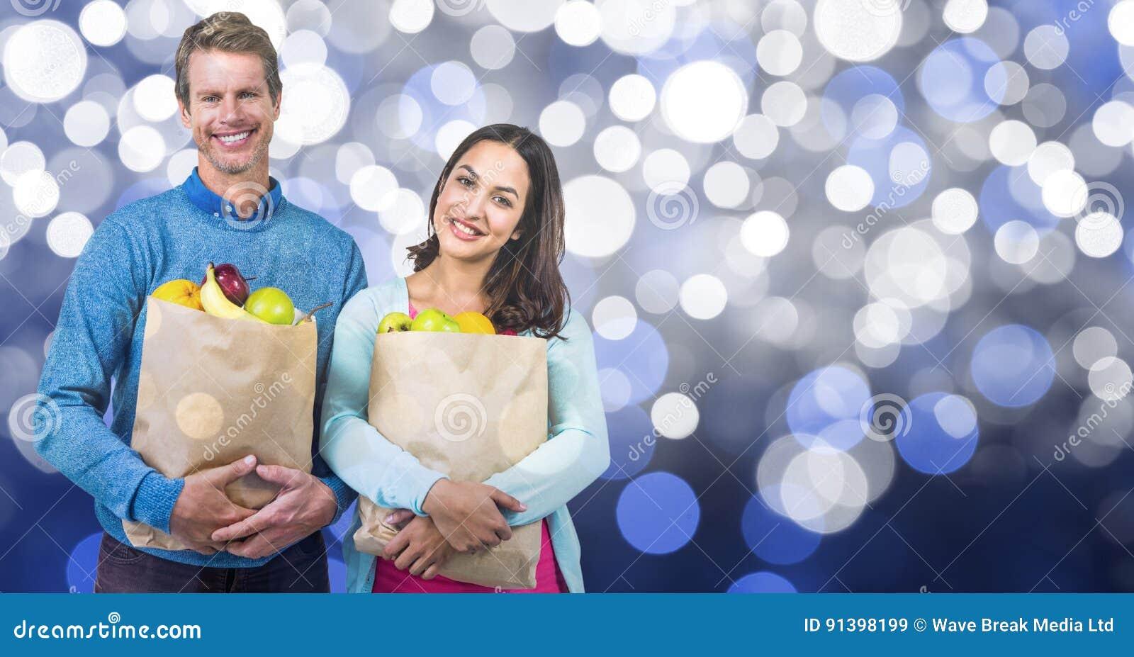 Bärande frukter för lyckliga par i pappers- påse över bokeh