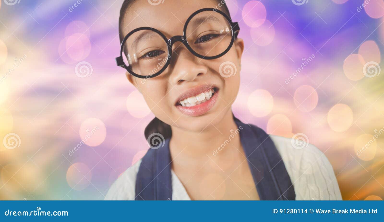 Bärande glasögon för liten flicka över suddighetsbakgrund