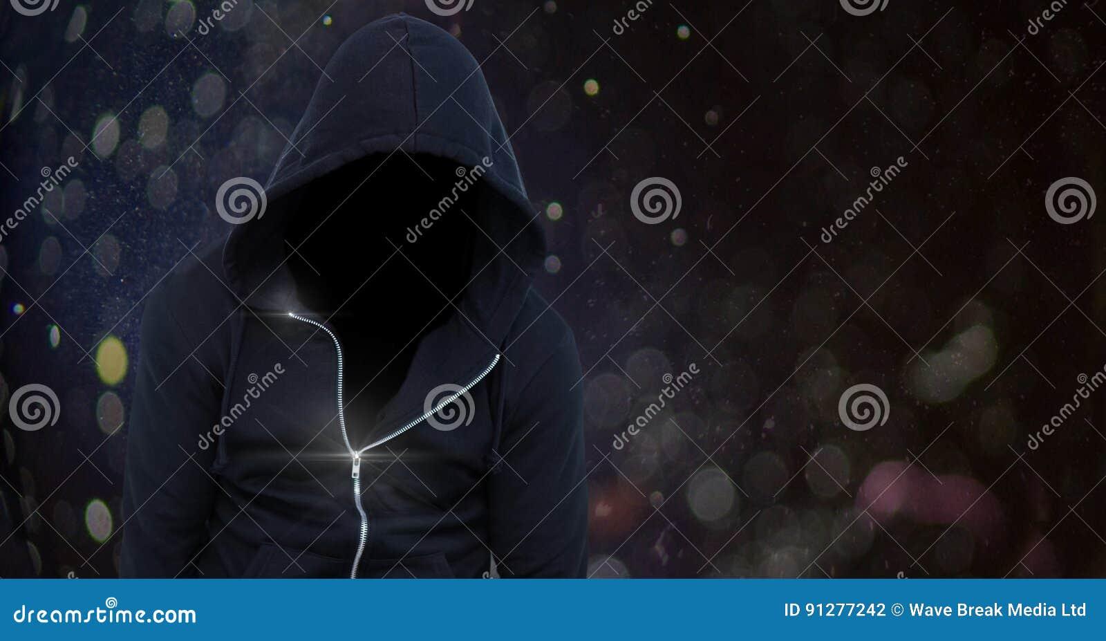 Bärande huv för anonym man framme av ljus